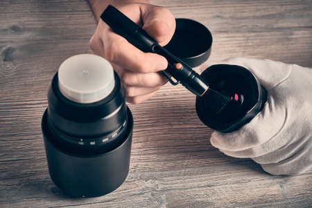 Man cleans photo lens with brush