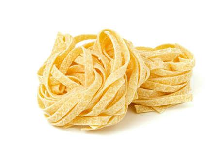 Uncooked tagliatelle pasta isolated on white