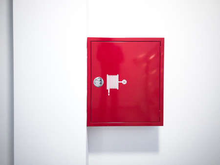 Red fire hose reel cabinet on wall