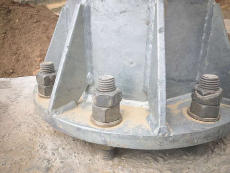 Metal pillar bolted to concrete foundation with anchor bolts