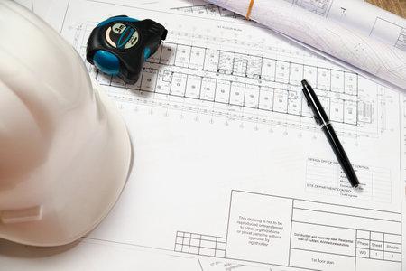 Hardhat, blueprint, measuring tape and pen