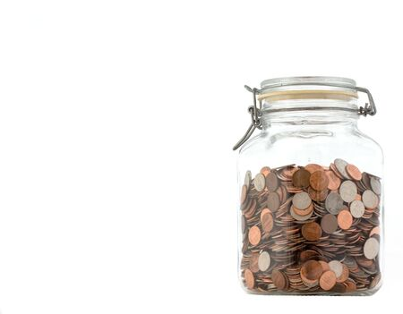 closed glass jar of assorted coins, against a white background