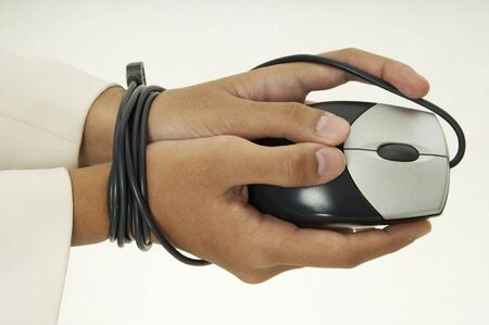 stifle: A woman holds a mouse and her hands are bound by the cable