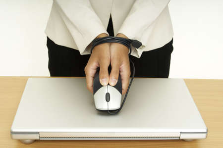 stifle: A woman holds a mouse over a laptop computer,her hands are tied up by the mouse cable Stock Photo