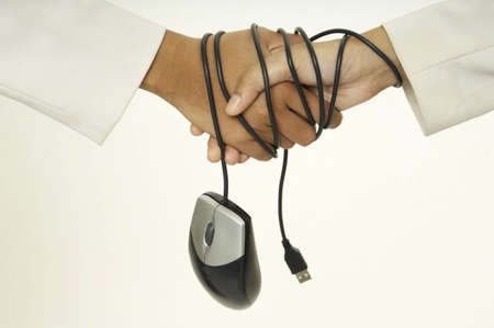 stifle: Two women shake hands and their wrists are bound by a mouse cable