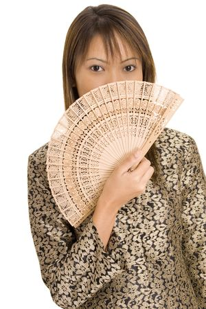 A pretty young asian girl holds a wooden fan in front of her face photo