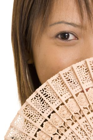 hides: An asian model hides behind a wooden fan