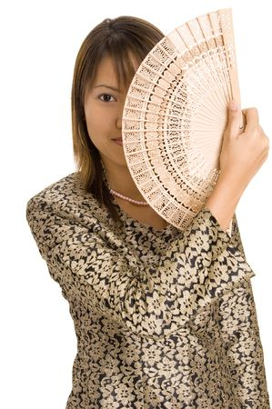 An attractive asian woman holds a wooden fan to cover half her face photo