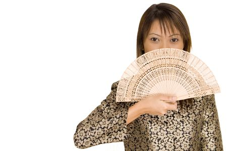 A pretty young asian model in traditional dress covers her face with a fan Stock Photo - 215461