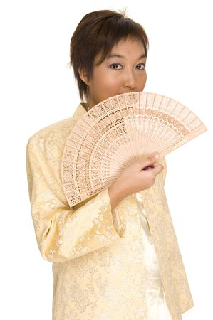 A pretty young asian model wears a yellow jacket and holds a wooden fan Stock Photo - 221058