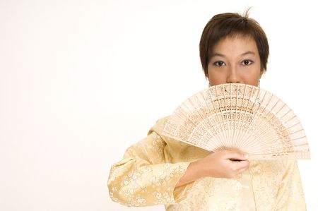 An asian girl in a yellow silk jacket holds a wooden fan to her face Stock Photo - 221056