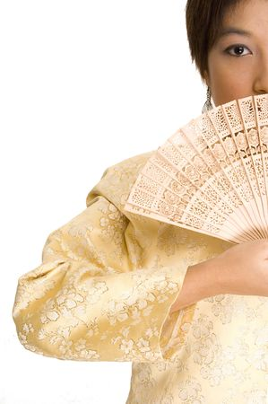 A pretty young asian girl wearing a yellow silk jacket hides her mouth with a wooden fan photo