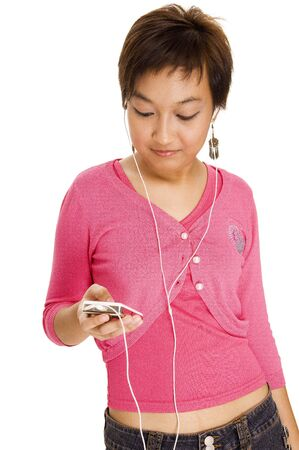 A young asian woman listens to music on a portable music device photo