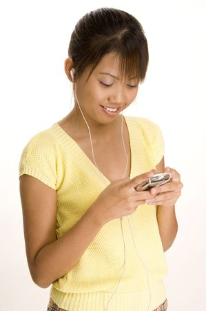 portable mp3 player: A young malay woman listens to music on her portable mp3 player