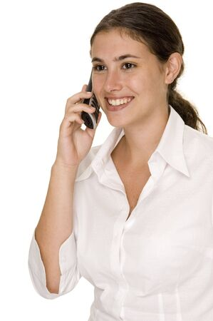 cordless phone: A young businesswoman smiles as she listens to someone talking on a cordless phone Stock Photo