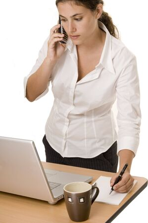 An attractive young businesswoman prepares to make notes. She is using a laptop whilst being on the phone photo