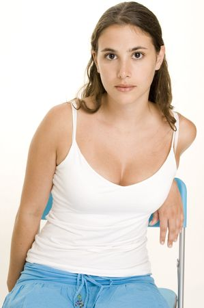 demure: An attractive young woman in a white top and blue skirt sits on a blue plastic chair