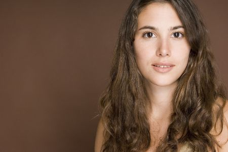 demure: A beautiful young woman with curly brown hair on a brown background