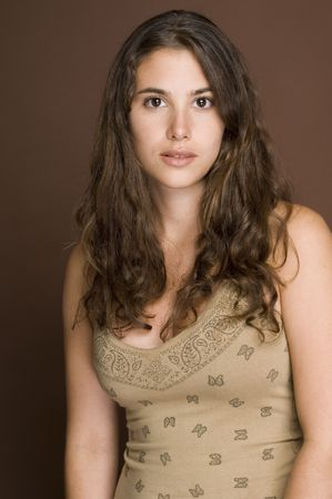 demure: A naturally beautiful young woman in a patterned top on a brown backdrop Stock Photo