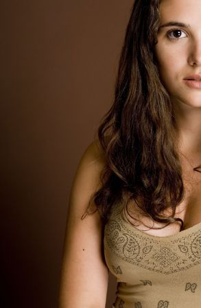 demure: A half-face shot of a beautiful young woman on a brown background Stock Photo