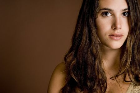 demure: A beautiful demure young woman on a brown backdrop