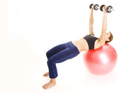 pectorals: A female fitness instructor demonstrates the finishing position of the dumbell press on a fitball