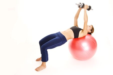 pectorals: A female fitness instructor demonstrates the finishing position of the dumbbell fly on a fitball