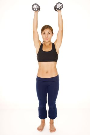 deltoids: A female fitness instructor demonstrates the finishing position of a dumbbell raise