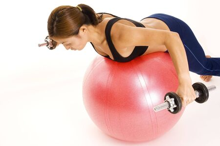 reverse: A female fitness instructor demonstrates the finishing position of the reverse fly on a fitball
