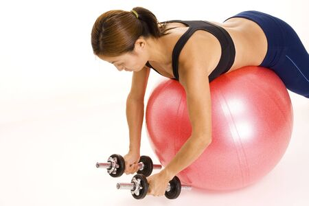 reverse: A female fitness instructor demonstrates the starting position of the reverse fly on a fitball Stock Photo