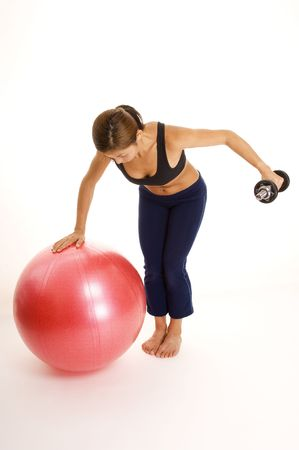 reverse: A female fitness instructor demonstrates a a one-arm reverse fly using a stability ball