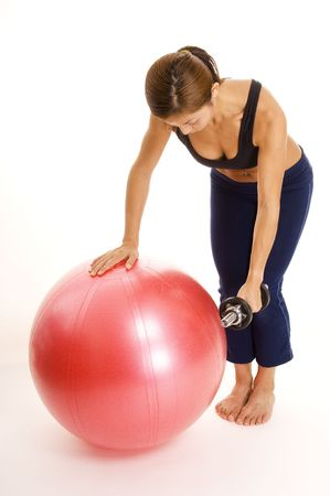 reverse: A female fitness instructor demonstrates a one arm reverse fly using a fitball Stock Photo