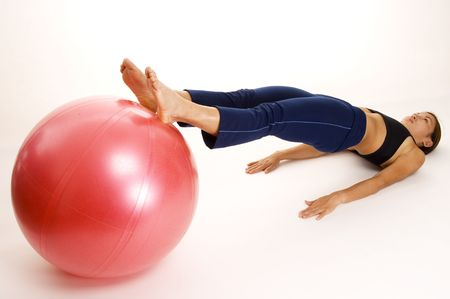 asian abs: A female fitness instructor demonstrates the finishing position of the Ball Rollout Stock Photo