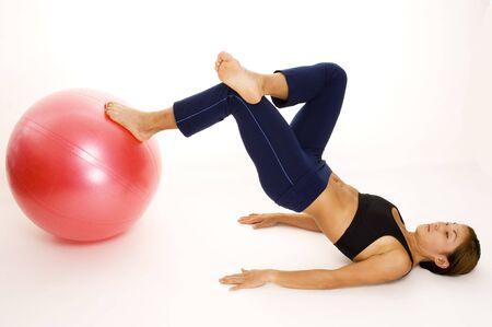A female fitness instructor demonstrates a one-legged bridge pose Stock Photo - 223210