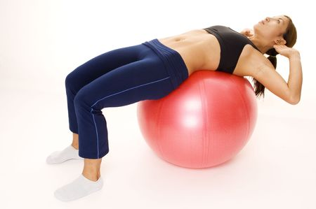 crunch: A female fitness instructor demonstrates an oblique crunch on a fitball Stock Photo