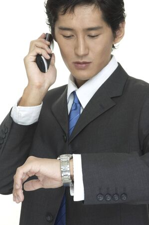 An asian businessman checks the time whilst talking on the phone Stock Photo - 227191