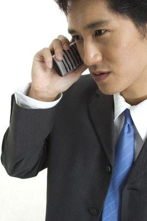 conversa: Un hombre de negocios asi�tico habla negocio en el tel�fono Foto de archivo
