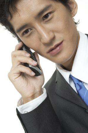 conversa: Un hombre de negocios asi�tico habla en el tel�fono Foto de archivo