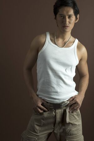 A muscular asian model in a white singlet and cargo pants photo