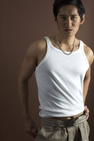 japenese: Un modelo masculino asian muscular en un chaleco blanco sobre un fondo marr�n  Foto de archivo