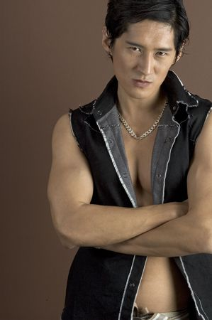 asian abs: A muscular asian male model in a black waistcoat on brown background