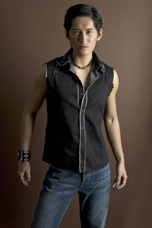 bloke: An asian male model in jeans and a waistcoat. Wearing a studded bracelet and other jewelry. Stock Photo