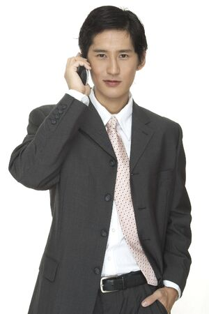 talks: an asian businessman in a grey suit talks on the phone