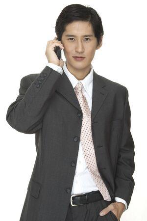 conversa: un hombre de negocios asi�tico en un juego gris habla en el tel�fono
