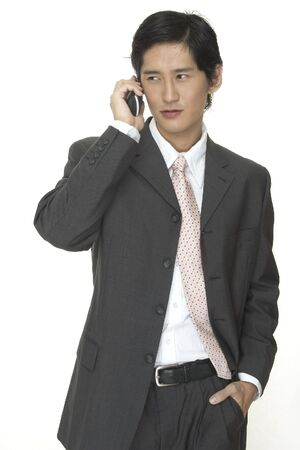 cordless phone: an asian businessman in a grey suit talks on a cordless phone Stock Photo