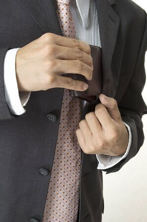 a businessman produces his wallet from his inside jacket pocket photo