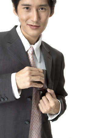 a smiling asian businessman in a grey suit takes his wallet from his jacket photo