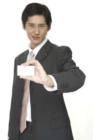 an asian businessman holds up his blank business card photo