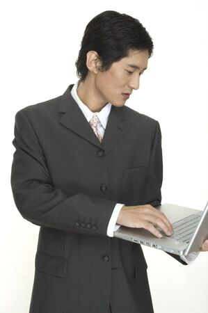 an asian businessman keeps up to date using his laptop computer photo