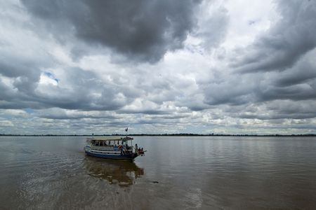 gather: A wooden tourist cruise boat looks vulnerable as storm clouds gather over the Mekong, Cambodia